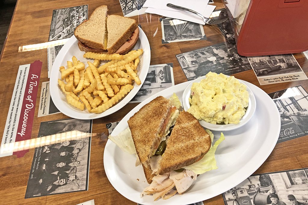 Two deli sandwiches with sides.