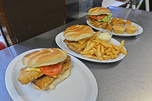 Three plated fish sandwiches. One is by itself, another has a side of french fries, and the last one has a side of cheese curds.